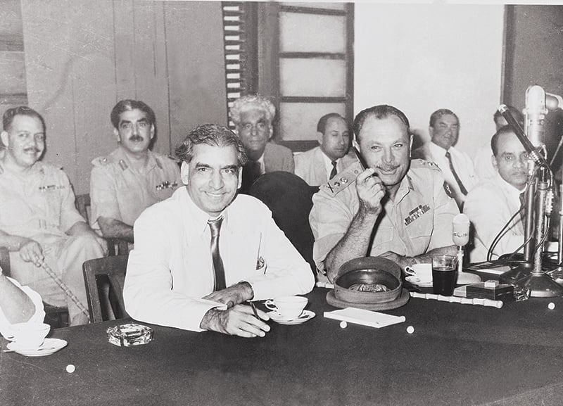 General Ayub Khan, Supreme Commander and Chief Martial Law Administrator, smiling after having addressed the nation on Radio Pakistan on October 8, 1958 – a day after he abrogated the Constitution and imposed Pakistan's first Martial Law. He is flanked here by senior bureaucrat Aziz Ahmed (left) and Lt-Gen Majeed Malik (right) who was instrumental in making it all happen. Seen behind them are Lt-Gen Yahya Khan (extreme left) and Zulfiqar Ali Bukhari (second from left). —  Photo: Hasan Bozai