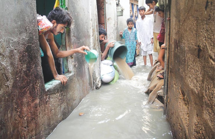 People drain rainwater from their homes located near Gujjar nullah in Nazimabad. —Agencies