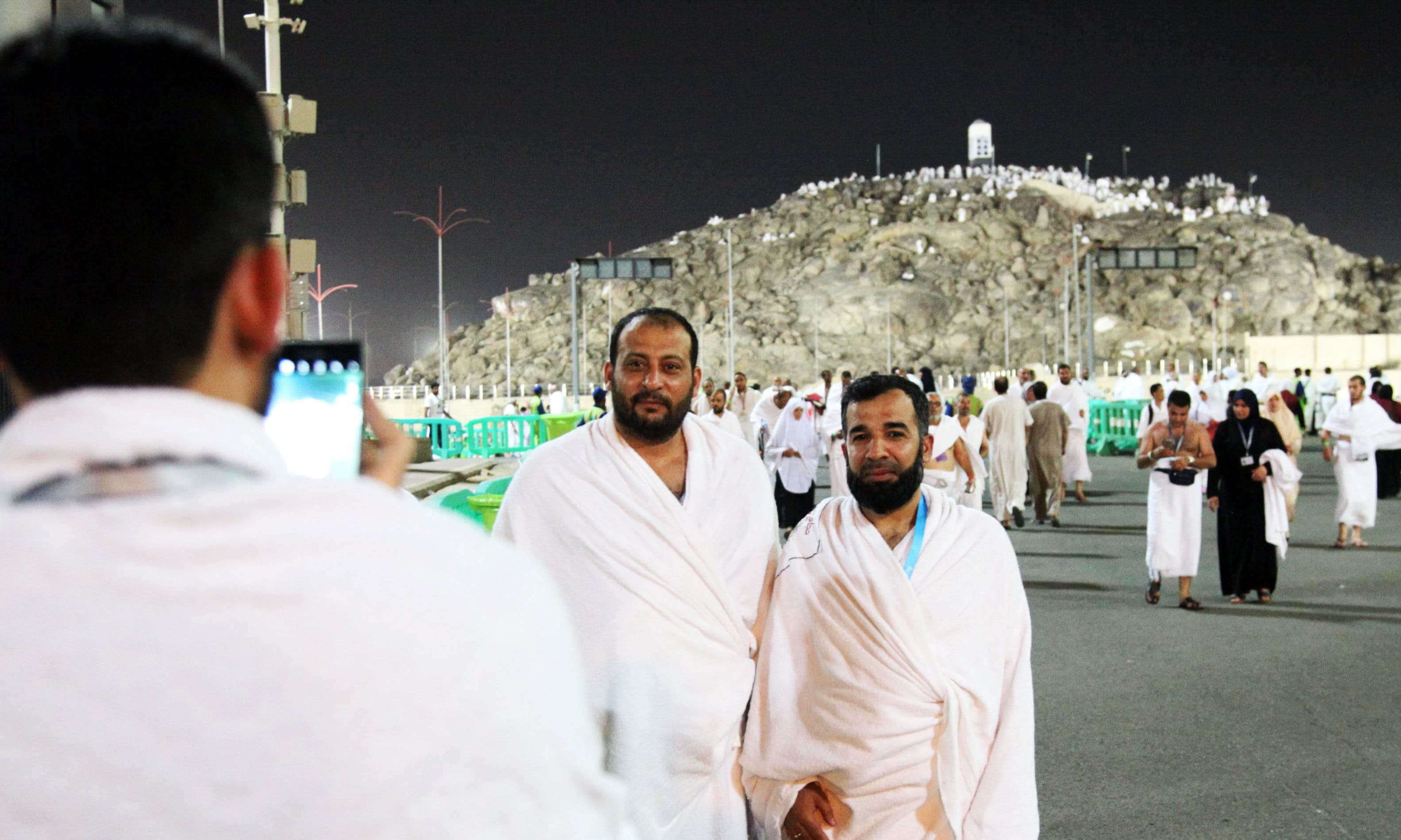 Pilgrims pose for a photo in front of Mount Arafat on the eve of Arafat Day.—AFP