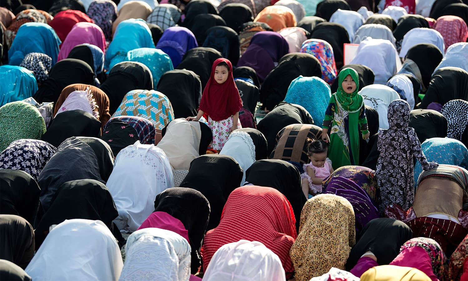 Girls looks on as worshippers gather to pray during Eidul Azha in Taguig, a suburb of Manila, Philippine.—AFP