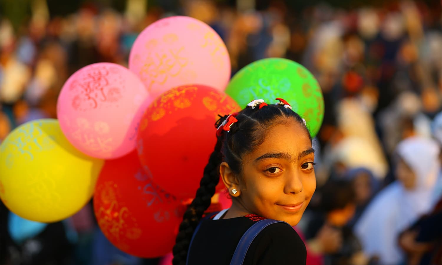 A Palestinian girl carries balloons while celebrating at the main square in Gaza City after performing the morning prayer for Eidul Azha.—AFP