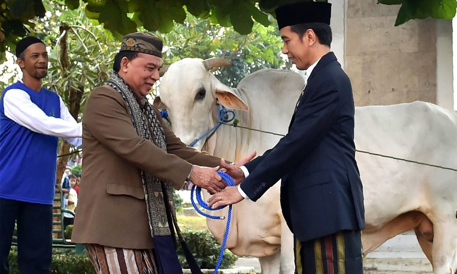 This handout from the Indonesian Presidential Palace shows Indonesia's President Joko Widodo (R) handing over cattle to be sacrificed after an Eidul Azha prayer in Sukabumi, West Java province.—AFP
