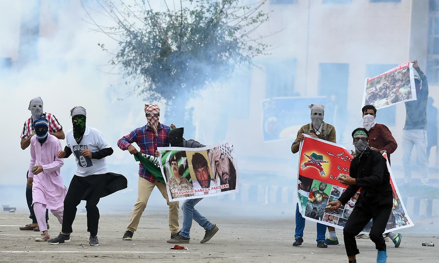 Kashmiri youth hold banners and throw stones during clashes between protesters and Indian government forces in downtown Srinagar.—AFP