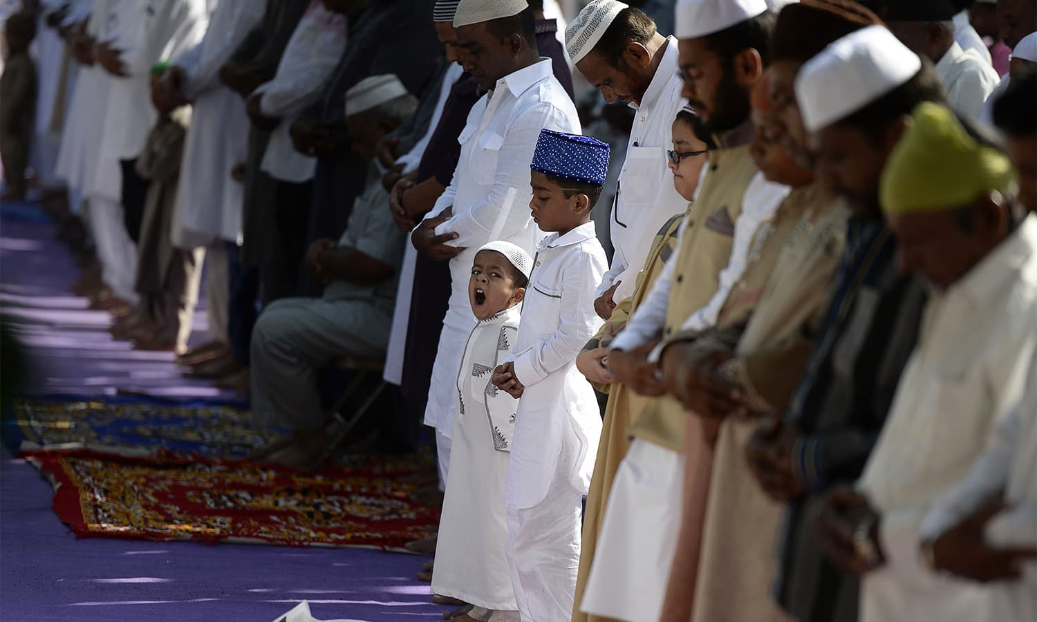 A young boy yawns as people offer Eid prayers in Hyderabad, India.—AFP