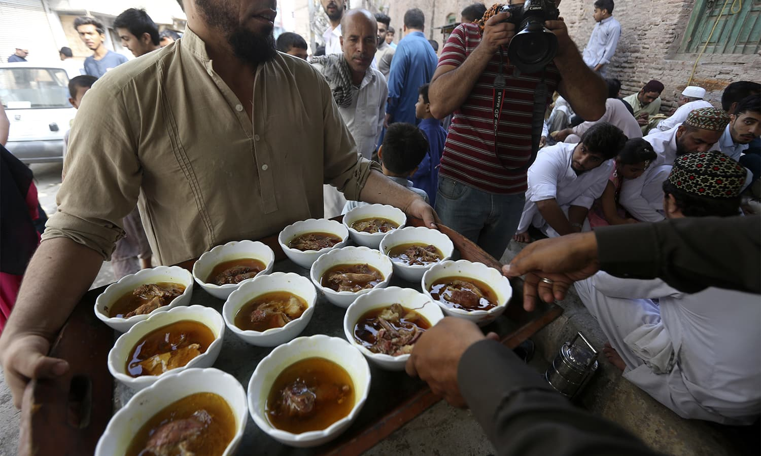 A man distributes food to people in Karachi on the first day of Eidul Azha.—AP