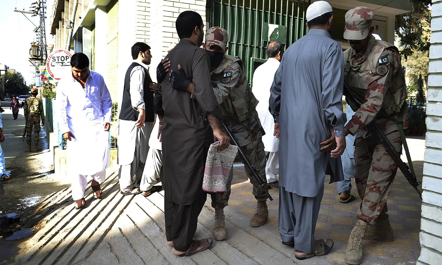 Rangers personnel search people arriving to offer prayers on the first day of Eidul Azha in Quetta.—AP