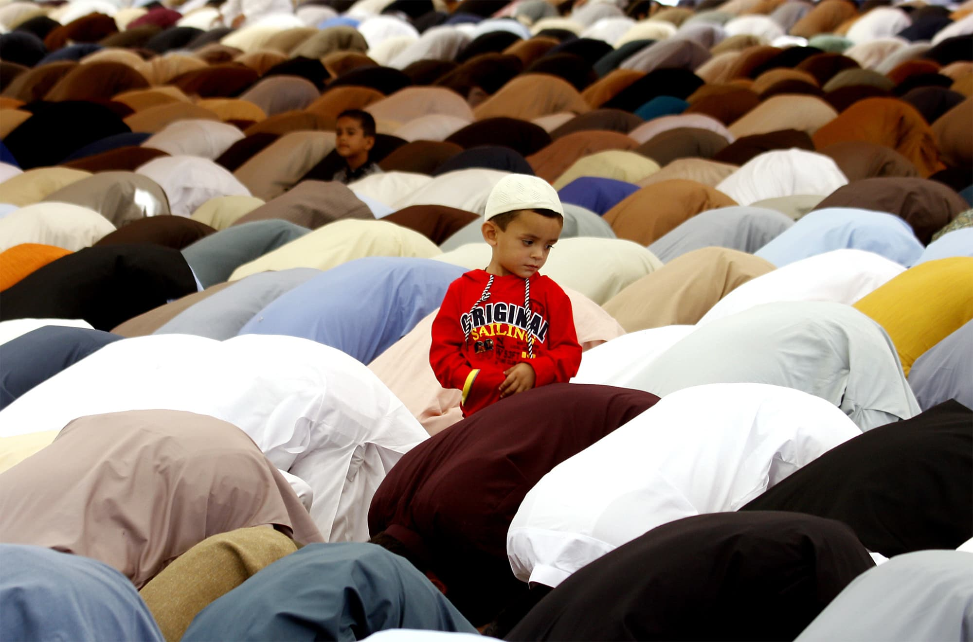 A boy stands amid worshippers offering Eid prayers in Quetta.—AP