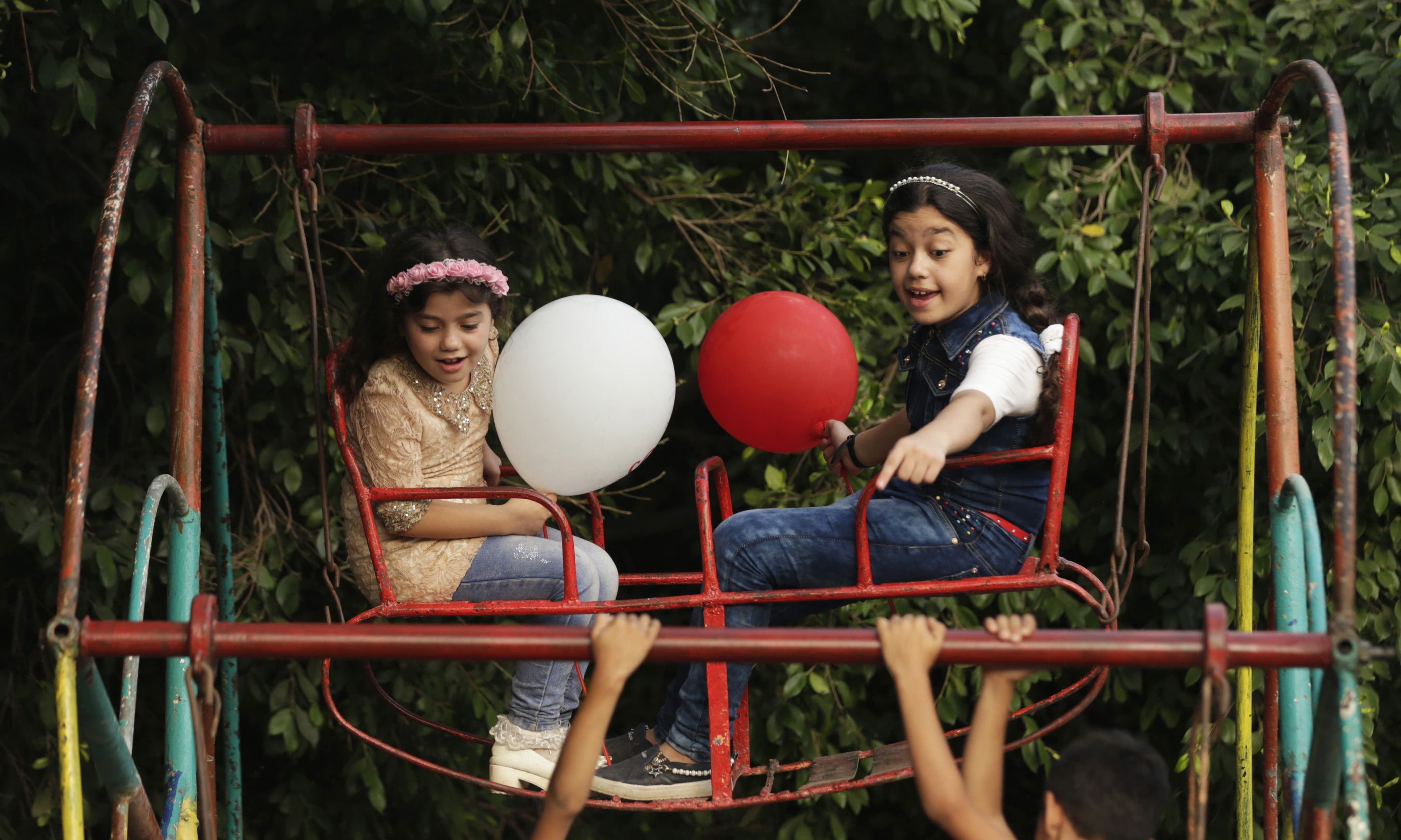 Palestinian children ride an attraction at an amusement park in Gaza City during Eidul Azha holiday. —AFP
