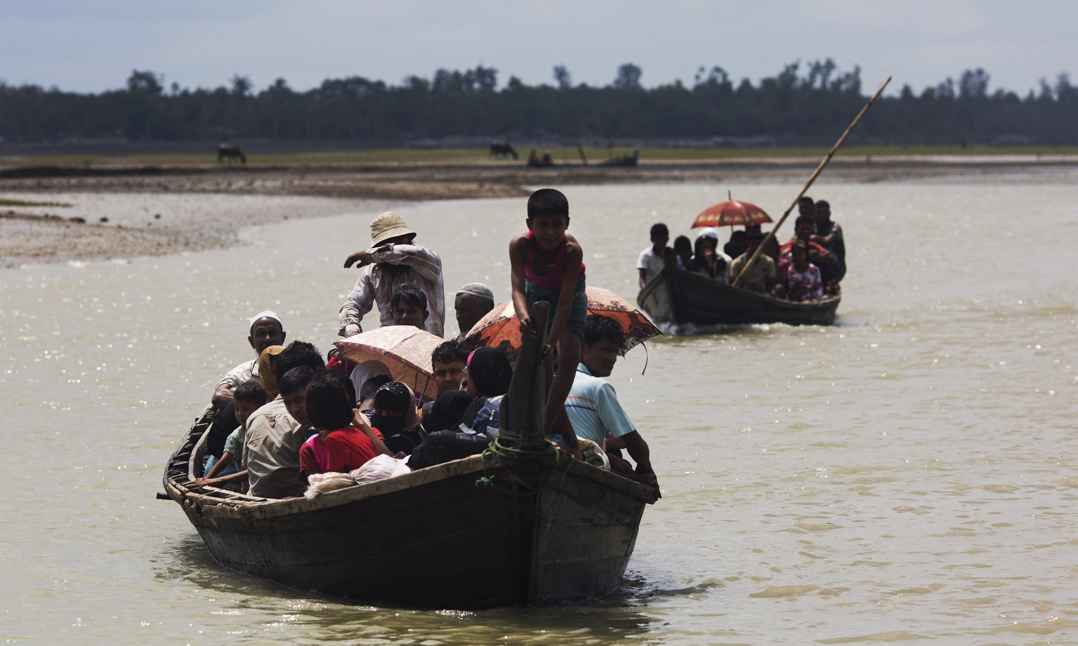 Myanmar's Rohingya ethnic minority use a local boat to cross a stream after crossing over to the Bangladesh side of the border near Cox's Bazar's Dakhinpara area. —AP