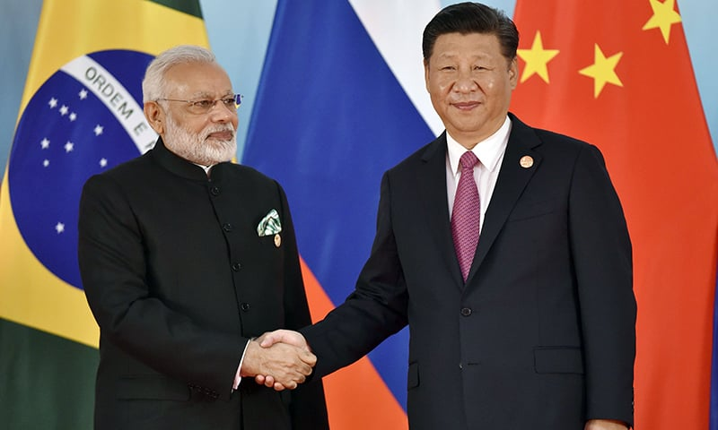 Chinese President Xi Jinping (R) and Indian Prime Minister Narendra Modi shake hands before the group photo. — AFP