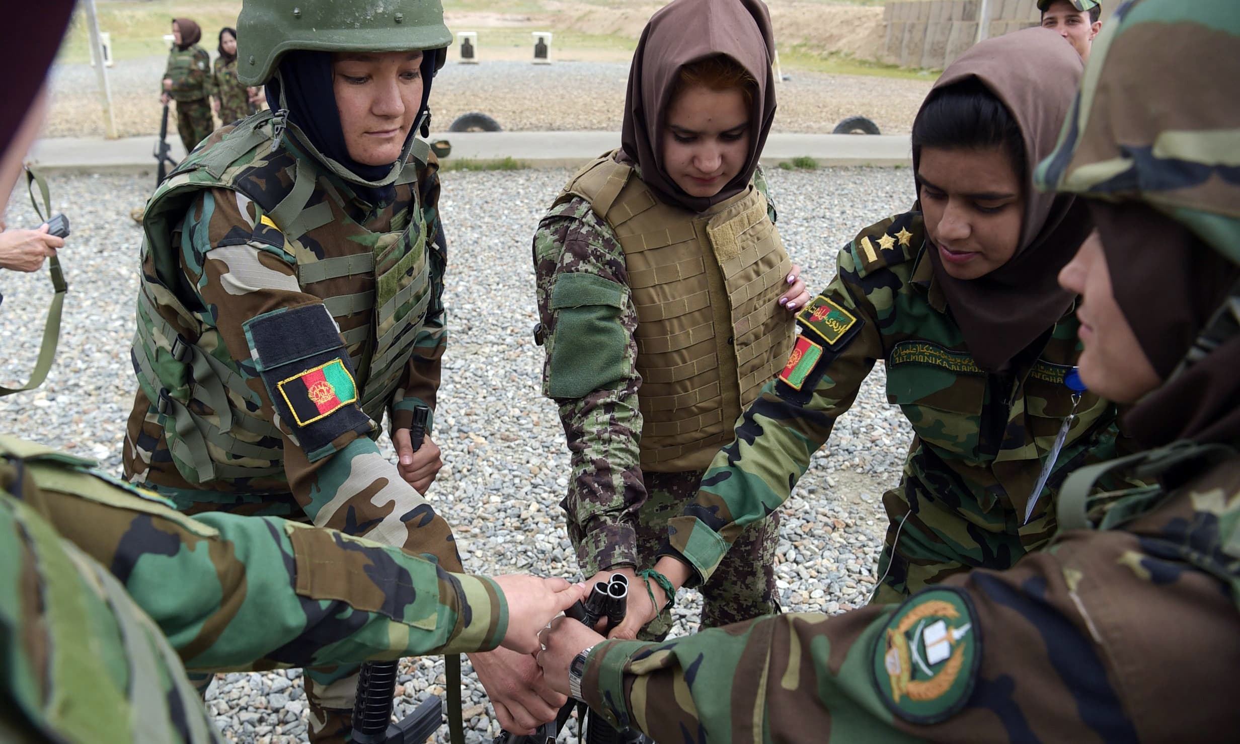 Female soldiers get their rifles at a range during a live firing exercise at the Kabul Military training centre on the outskirts of Kabul. —AFP