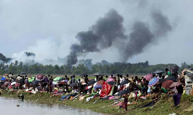 میانمار کی ریاست رخائن کے ایک گاؤں سے دھویں کے بادل اٹھ رہے ہیں جبکہ روہینگیا مسلمانوں کا ایک گروپ میانمار اور بنگلہ دیش کے درمیان نومین لینڈ میں پناہ لیے ہوئے ہے — اے ایف پی فوٹو