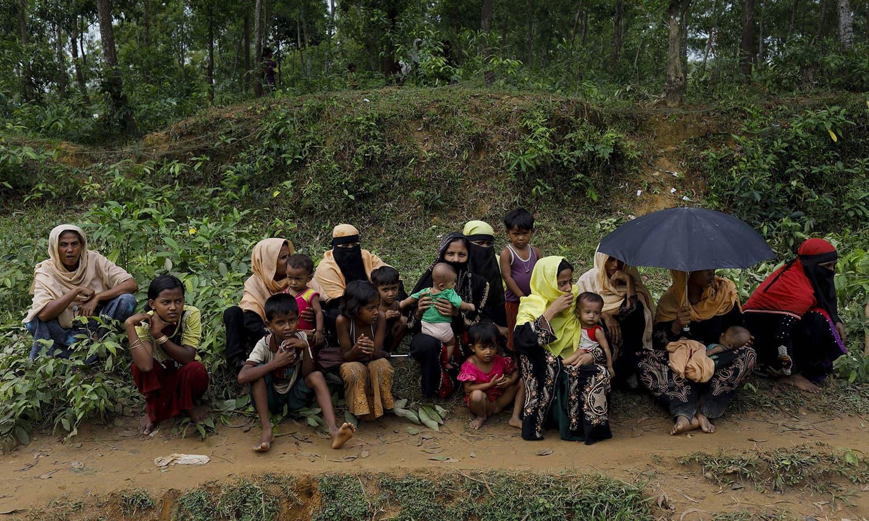 میانمار سے جان بچا کر بنگلہ دیش پہنچنے والے روہنگیا افراد ایک سڑک کے کنارے بیٹھے ہوئے امداد کے منتظر ہیں — اے ایف پی فوٹو