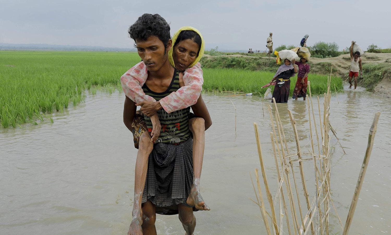 ایک نوجوان خاتون کو کندھے پر اٹھائے رخائن سے بنگلہ دیش کی سرحد عبور کررہا ہے — اے ایف پی فوٹو
