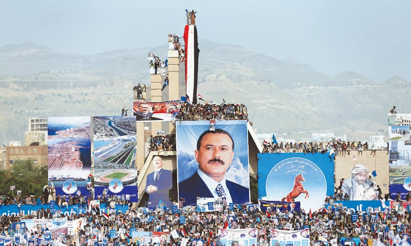 SUPPORTERS of Yemen's former president Ali Abdullah Saleh (pictured in poster) gather at the Monument of the Unknown Soldier during a rally to mark the 35th anniversary of the establishment of the General Peoples Congress in Sanaa on August 24.—Reuters