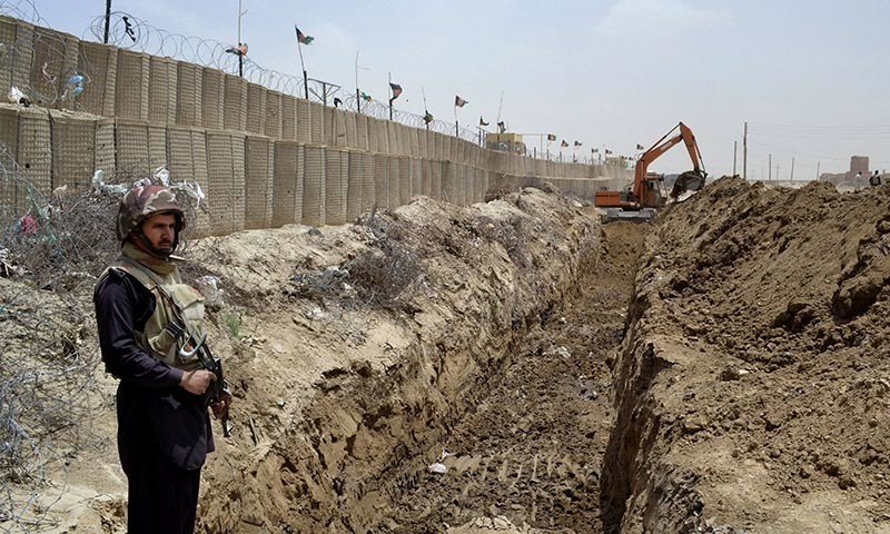 In this May, 16, 2014 photo, a Pakistani border guard stands alert as an excavator digs a trench along Pakistan-Afghanistan border at Chaman post in Balochistan.— AP