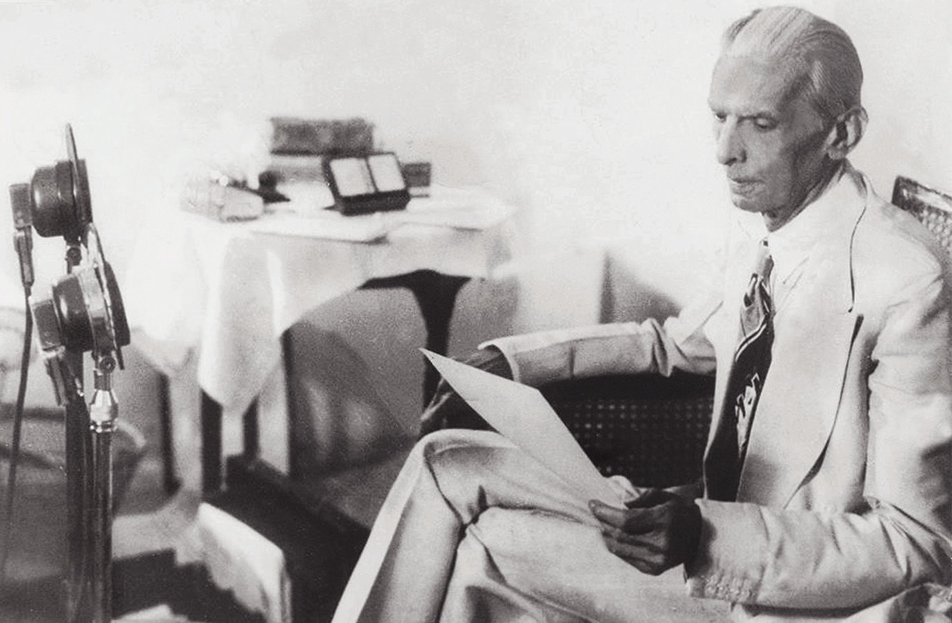 Quaid-i-Azam Mohammad Ali Jinnah is seen having a last look at the speech draft as he was about to speak on All-India Radio on June 3, 1947, in Delhi, soon after the announcement by Lord Mountbatten of the British Government's Partition Plan. | Photo: The Press Information Department, Ministry of Information, Broadcasting & National Heritage, Islamabad (PID)