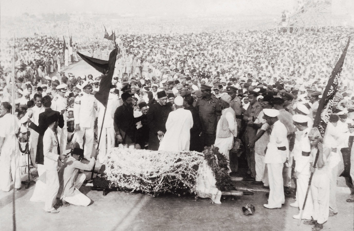 A view of Quaid-i-Azam Mohammad Ali Jinnah's funeral on September 12, 1948, at the Exhibition Ground in Karachi. Nawabzada Liaquat Ali Khan (centre) is seen conferring with Maulana Shabbir Ahmed Usmani (in a white shalwar kameez), as he prepared to lead the funeral prayers. | Photo: The Press Information Department, Ministry of Information, Broadcasting & National Heritage, Islamabad (PID)