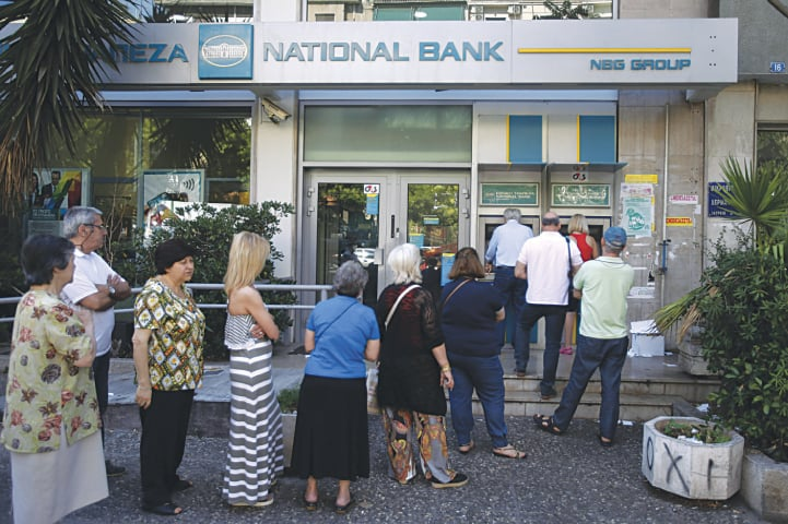 People queue at an ATM outside a bank in Athens | AP