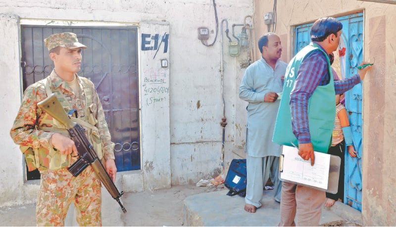 A Rangers' personnel stands guard as census staff carry out their duty