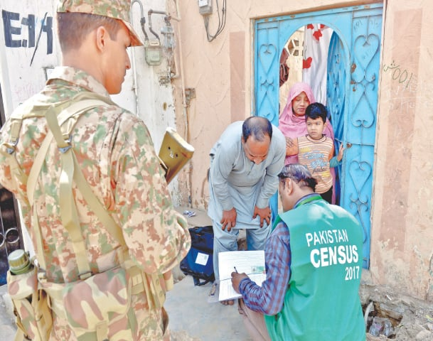 A census enumerator flanked by security personnel collects data