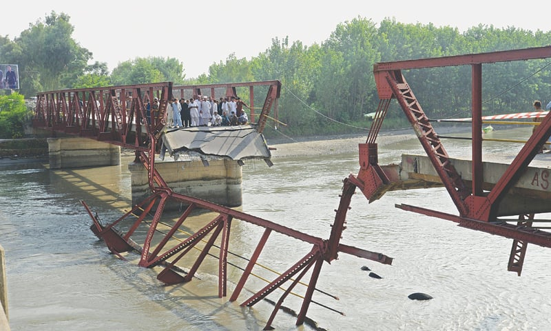 CHARSADDA: People gather after a British-era bridge on the Kabul river gave way on Saturday. A part of the bridge broke and collapsed when a truck carrying over 1,000 cement bags was passing through it. —Shahbaz Butt / White Star