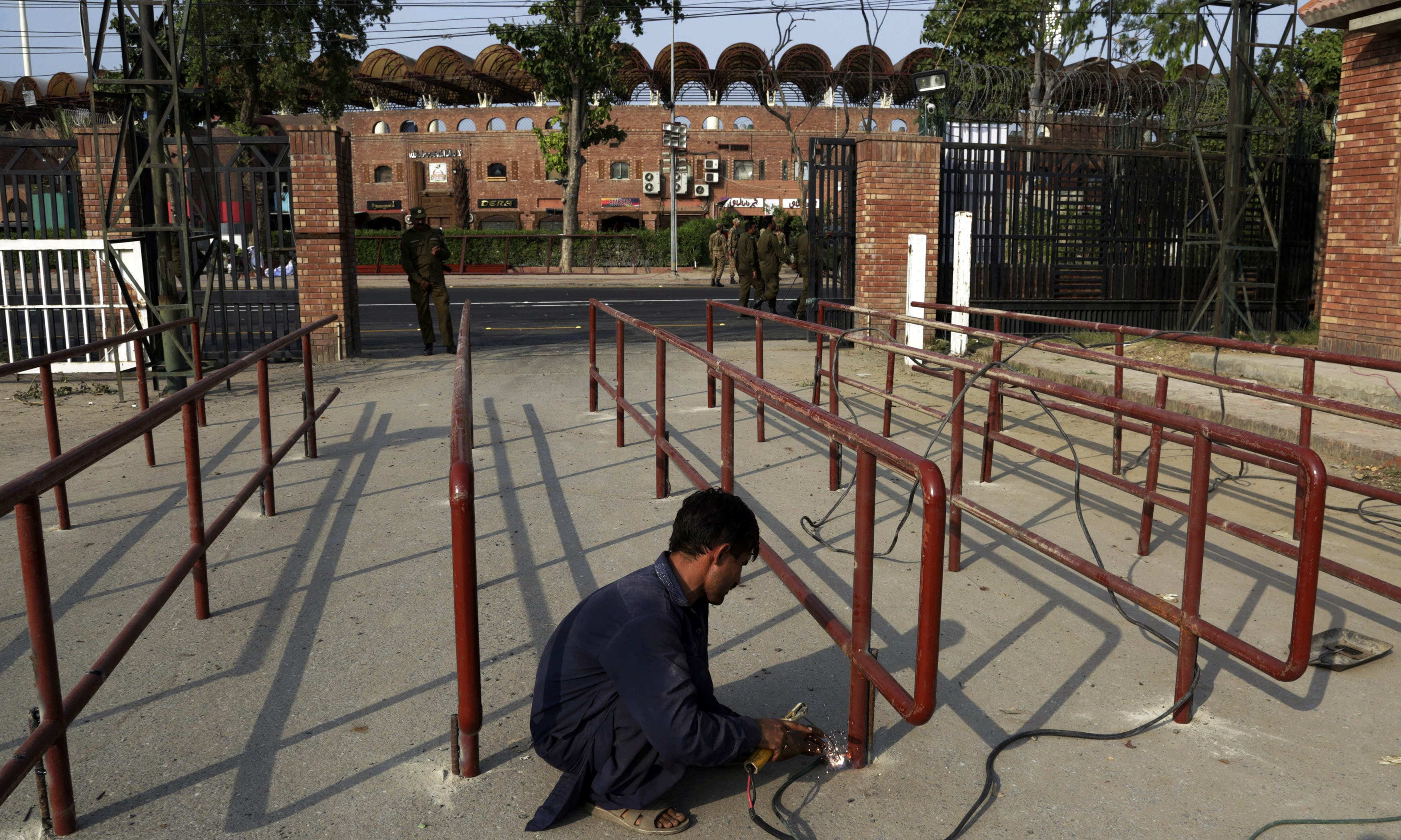 A worker welds a barrier at an entrance to the  Gaddafi stadium, in preparation for the World XI series in Pakistan. —AP