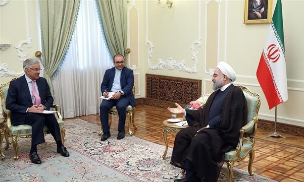 Foreign Minister Khawaja Asif and Iranian President Hassan Rouhani discuss bilateral relations on Sept 11. — Photo courtesy FO
