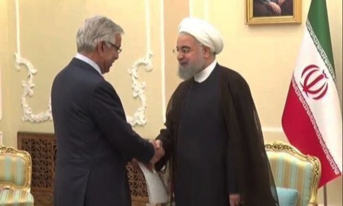 Iran President Hassan Rouhani greets Foreign Minister Khawaja Asif on Sept 11. —Photo courtesy Foreign Office
