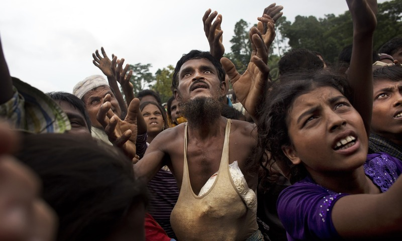 A Rohingya man stretches his arms out for food distributed by local volunteers, with bags of puffed rice stuffed into his vest at Kutupalong, Bangladesh on Saturday.— AP