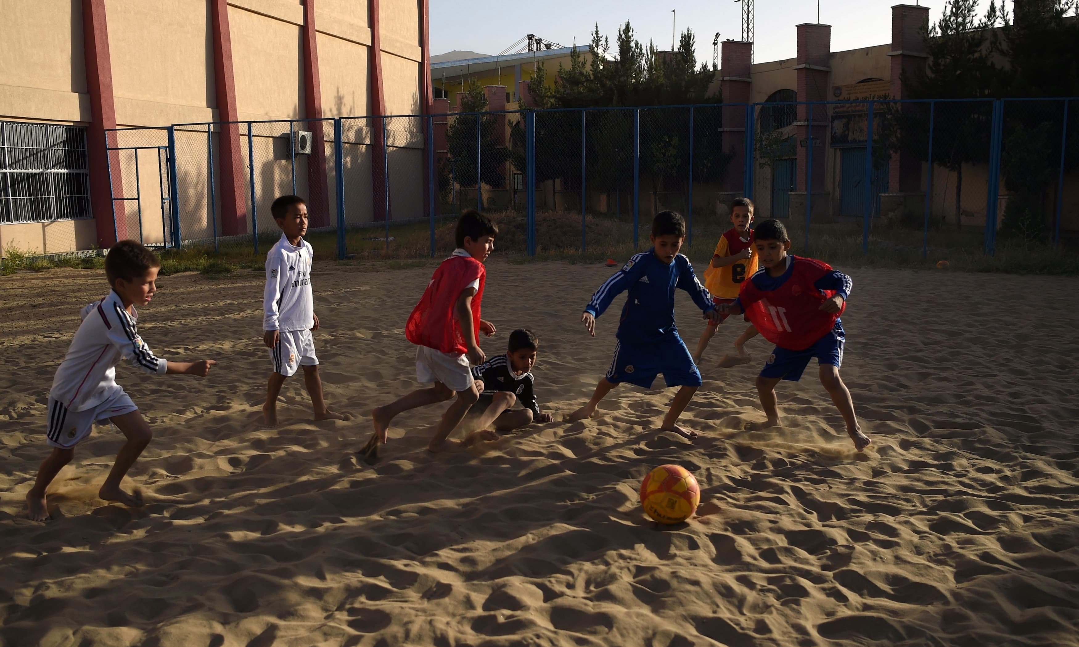 Afghan youth play beach football at Ghazi stadium in Kabul. —AFP