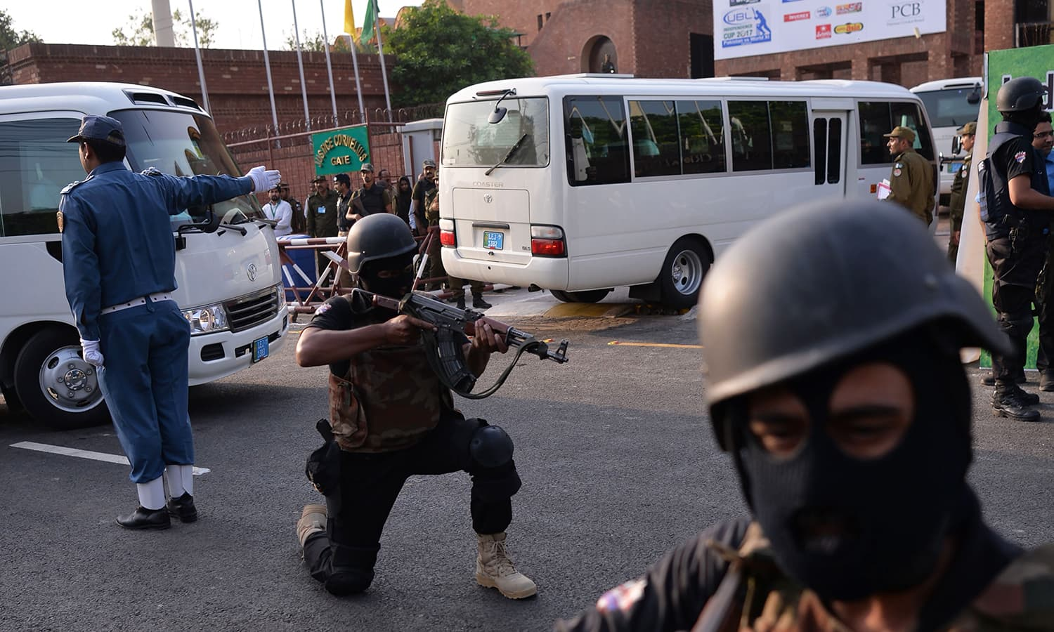 Police commandos take position as they escort a street on the arrival of World XI players for practice at the Gaddafi Stadium. — AFP