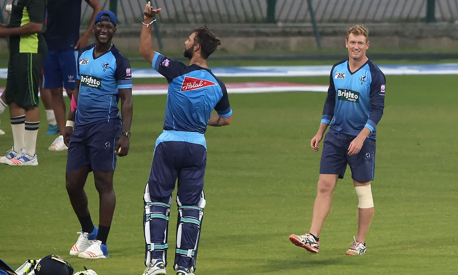 World XI cricketers George Bailey, Darren Sammy and Grant Elliott take part in a practice session at the Gaddafi Stadium.— AFP