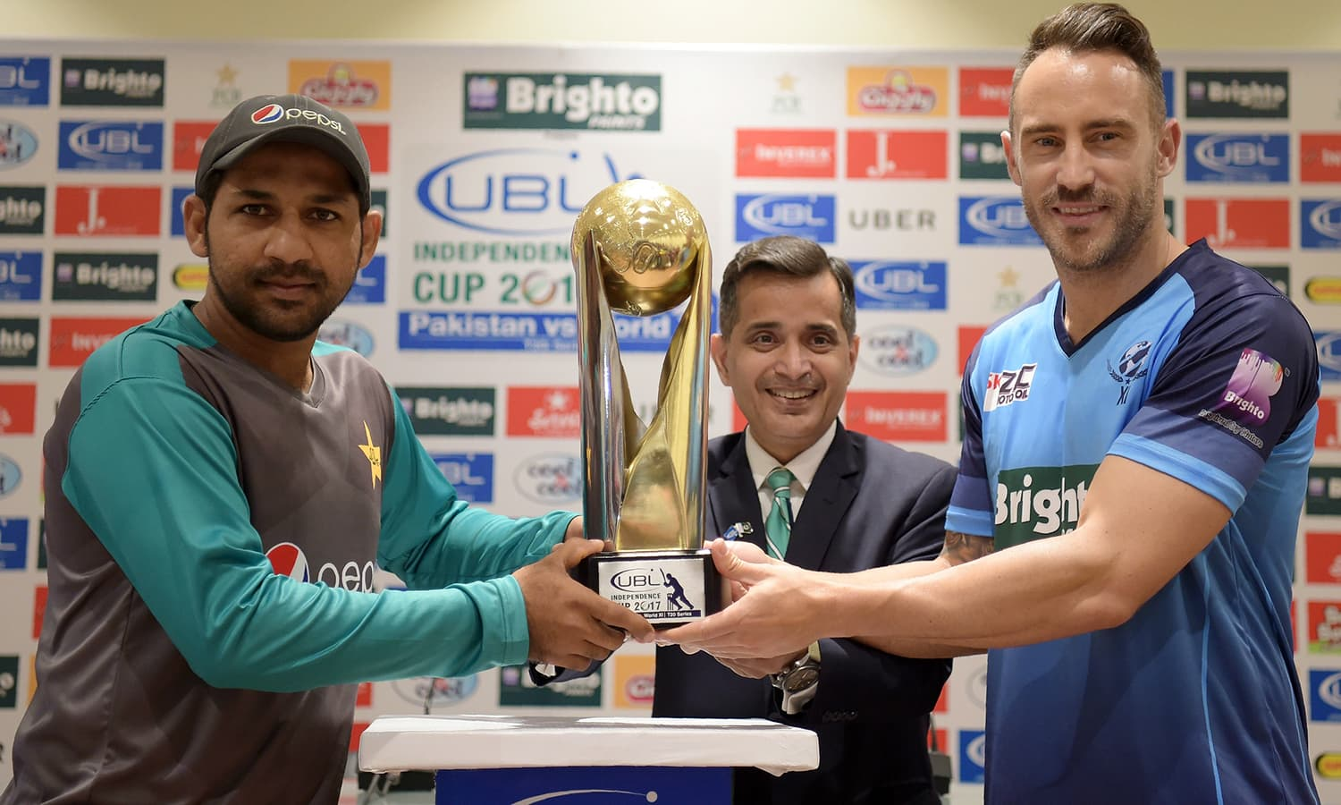 Pakistan captain Sarfraz Ahmad (L) and World XI captain Faf du Plessis hold the Independence Cup trophy during a ceremony at the Gaddafi Stadium.— AFP