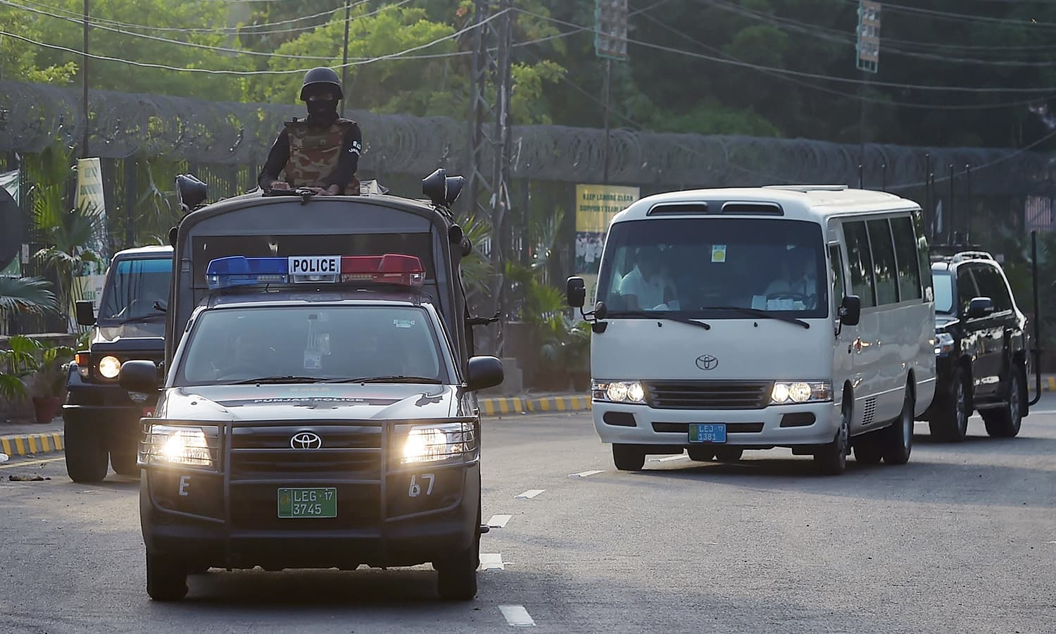 Security personnel escort a bus carrying World XI players as they arrive at the Gaddafi Stadium.— AFP