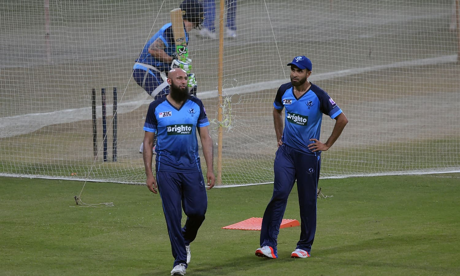 World XI cricketers Hashim Amla (L) and Imran Tahir (R) take part in a practice session at the Gaddafi Stadium in Lahore.— AFP
