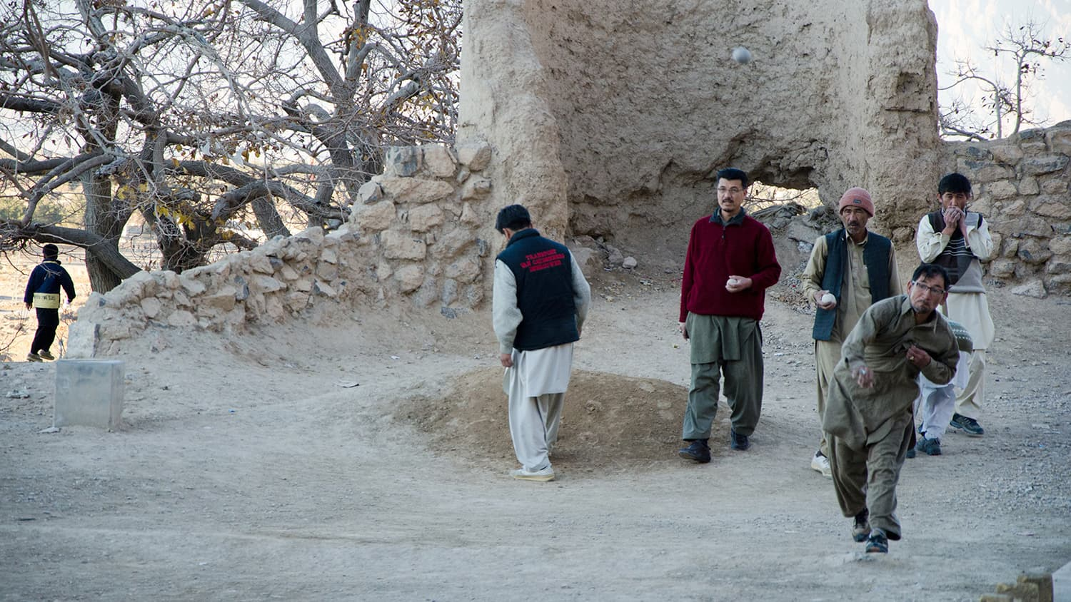 A man throwing a stone at the qarqa in the game known as Sang Girag. People of all ages gather to watch the game of Sang Girag.