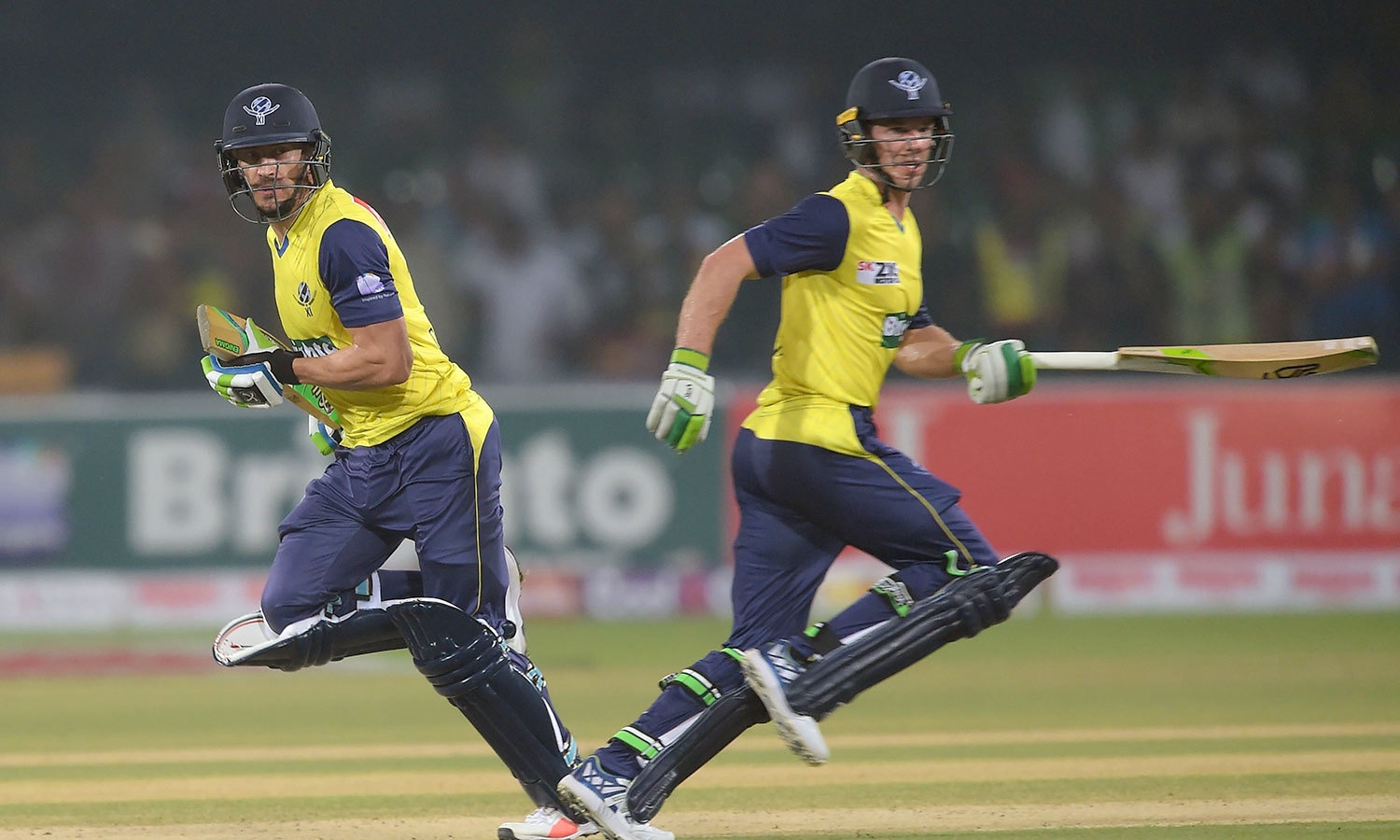 World XI captain Faf du Plessis (L) and teammate Tim Paine run between the wicket during the first Twenty20 international match between the World XI and Pakistan at the Gaddafi Stadium in Lahore on September 12, 2017. —AFP