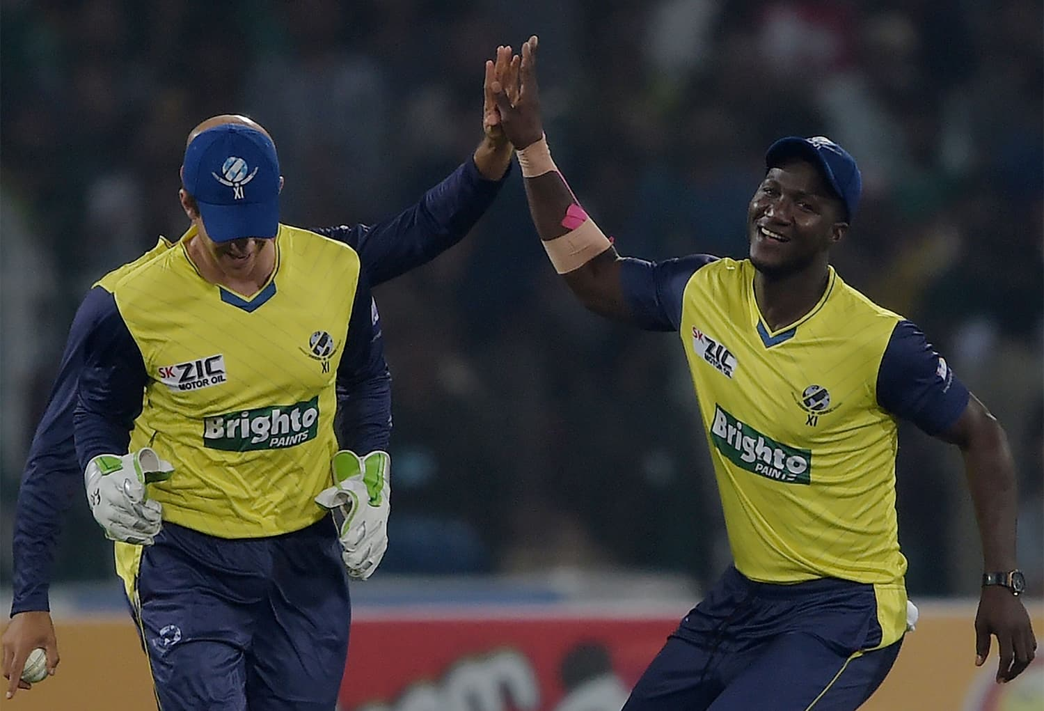 World XI cricketer Darren Sammy (R) celebrates after the dismissal of Fakhar Zaman during the first Twenty20 international match between the World XI and Pakistan at Gaddafi Stadium in Lahore. ─AFP