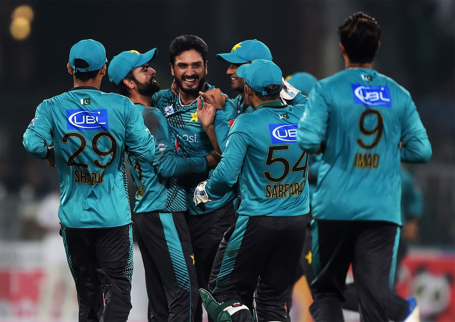 Rumman Raees (C) celebrates with teammate Ahmed Shehzad after taking the wicket of World XI batsman Tamim Iqbal. ─AFP