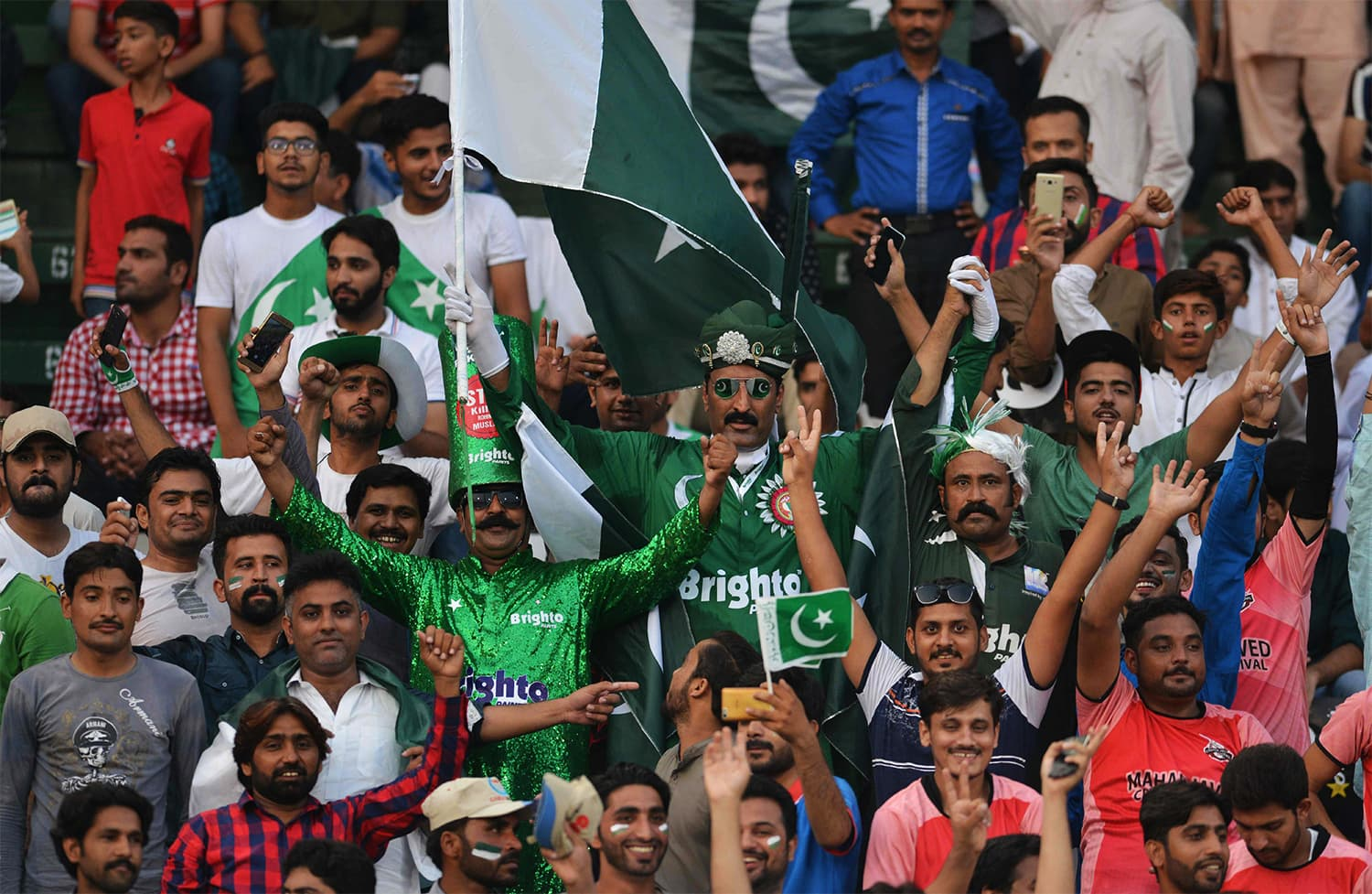 Spectators cheer at the start of the first T20I between the World XI and Pakistan at Gaddafi Stadium. ─ AFP