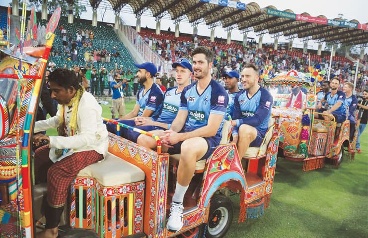 LAHORE: Members of the World XI ride in traditionally-decorated rickshaws before the start of their first Twenty20 cricket match against Pakistan's team on Tuesday.—AP