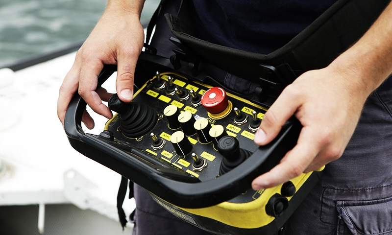 Frank Marino, an engineer with Sea Machines Robotics, uses a remote control belt pack to control a self-driving boat in Boston Harbor.—AP