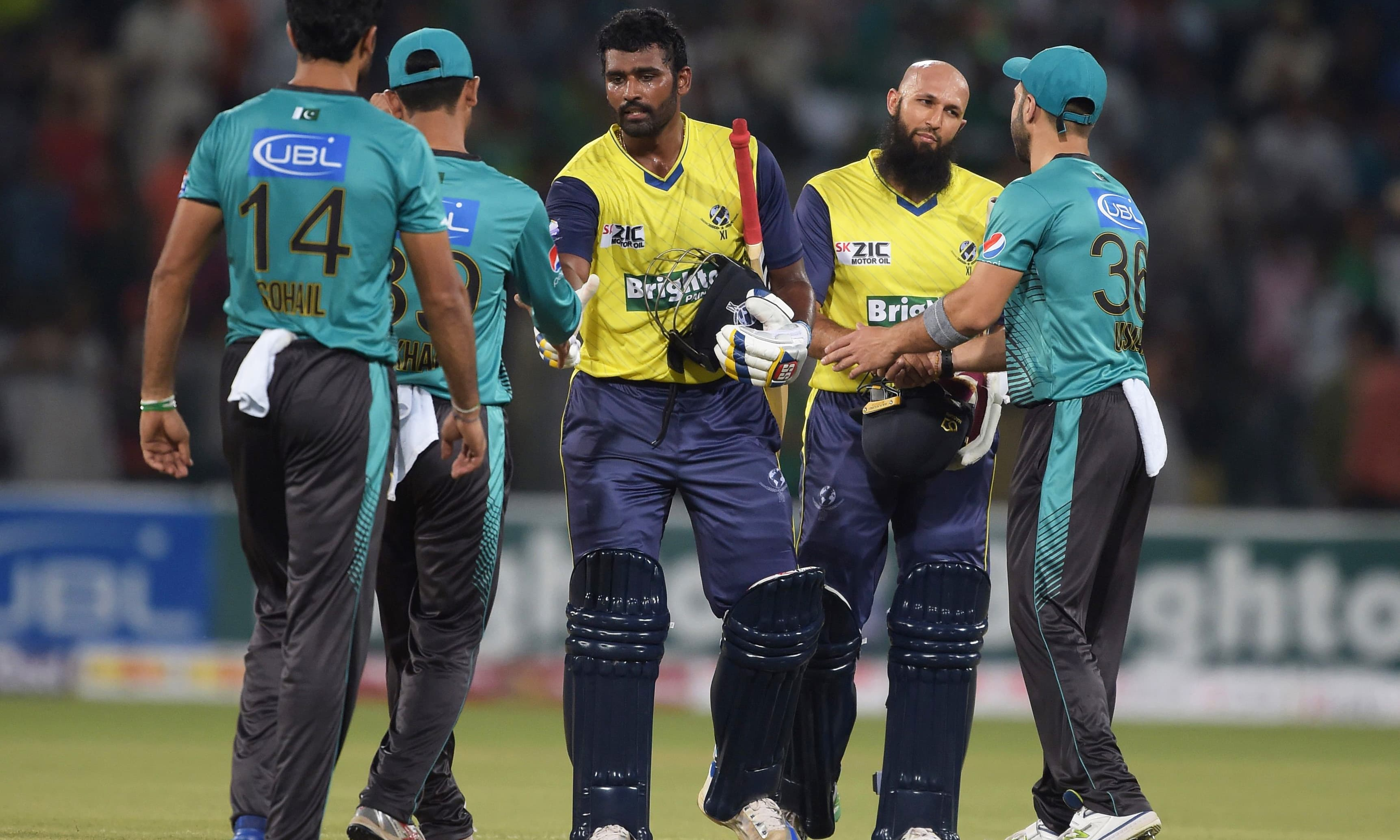 World XI batsmen Hashim Amla (2R) and Thisara Perera (C) shake hands with Pakistani cricketers at the end of the second match. —AFP