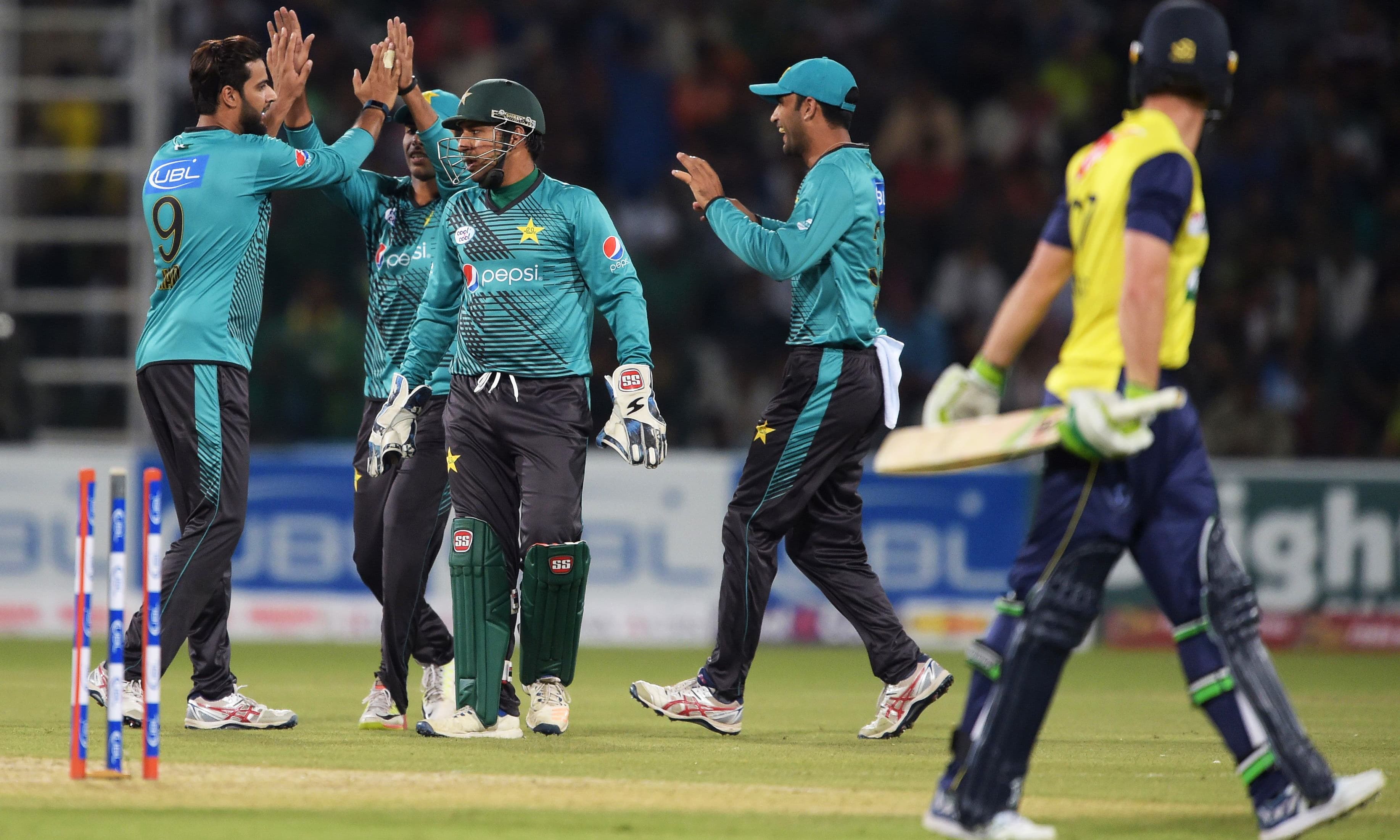 Pakistani spinner Imad Wasim (L) celebrates with teammates after taking the wicket of World XI batsman Tim Paine (R). — AFP