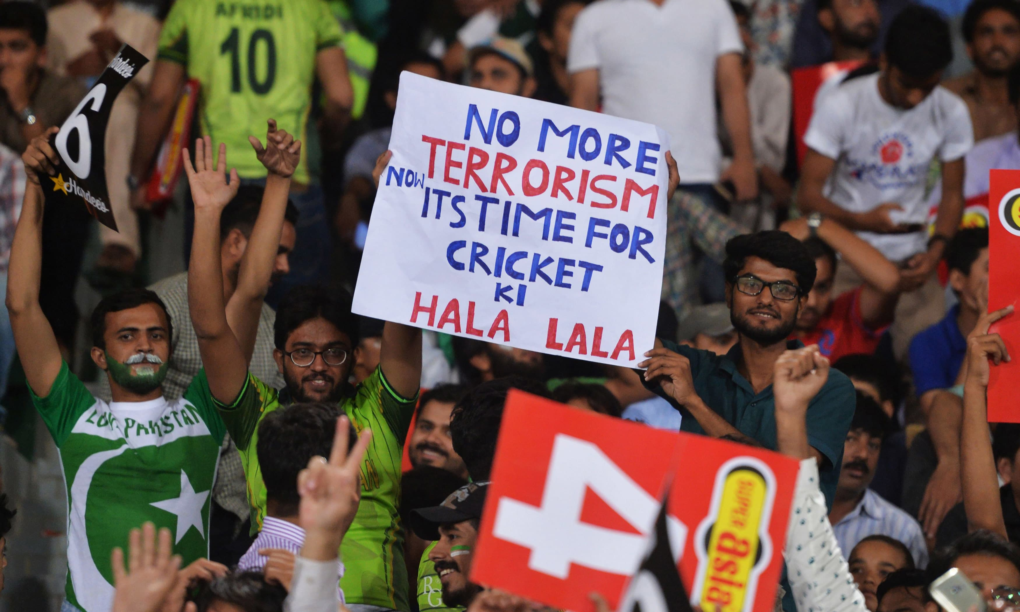 Spectators hold placards during the second T20 International match between the World XI and Pakistan. — AFP