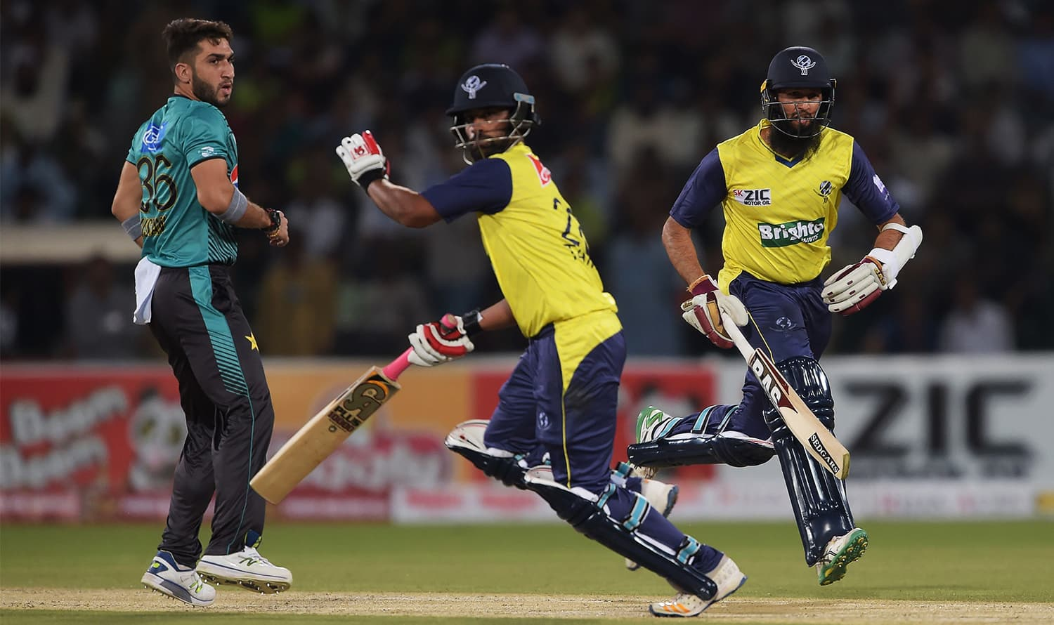 World XI batsmen Hashim Amla (R) and Tamim Iqbal (C) run between the wicket as bowler Usman Shinwari looks on. ─ AFP