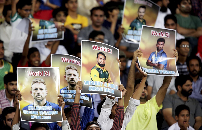 میدان میں موجود شائقین نے ورلڈ الیون کے کھلاڑیوں کے پوسٹرز تھامے رکھے ہیں— فوٹو: اے ایف پی