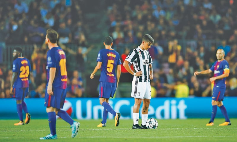 BARCELONA: Juventus' Paulo Dybala stands dejected as Barcelona's Lionel Messi (second L) celebrates after scoring during their Group 'D' clash at the Camp Nou.—AP