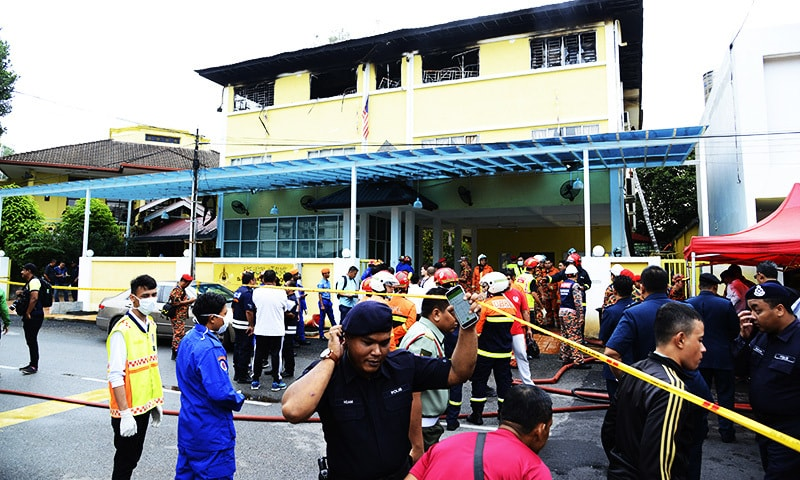 Police and rescue personnel work at an Islamic religious school cordoned off after the fire on the outskirts of Kuala Lumpur .—AP
